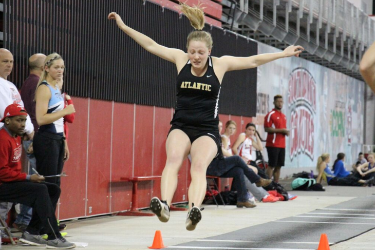 Senior Alaena Pelzer lifts off into the sand pit at the USD indoor track meet.