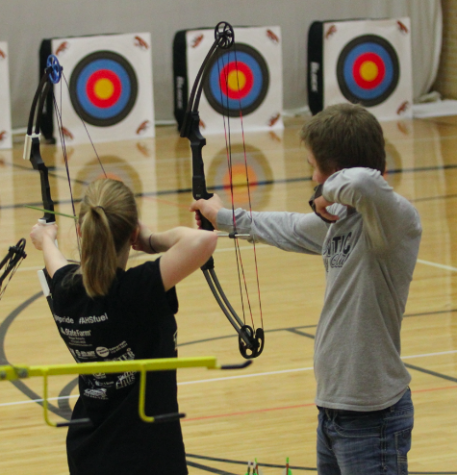 Two archers pull their arrows back as they prepare to shoot.