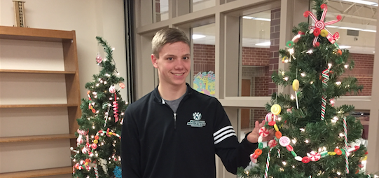O CHRISTMAS TREE(S)-Sophomore Zade Niklasen admires the Christmas trees' sparkling lights in the library.  The trees were placed by the window so anyone that passed by the library could get a glimpse of the Christmas trees.  These were only two of many Christmas trees set up in the school.