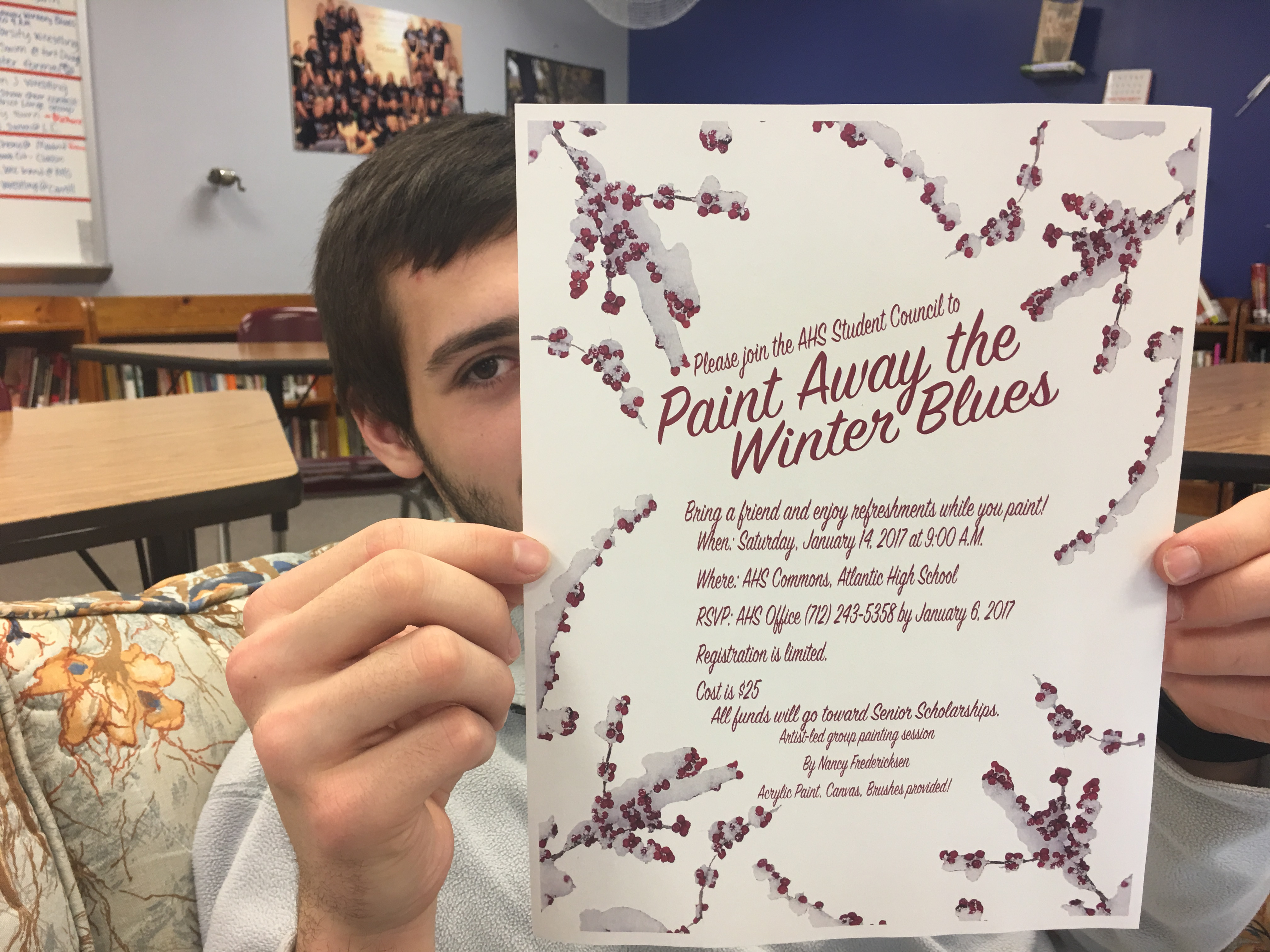 Zeke Whetstone displays the poster advertising STUCO's fundraiser, Paint Your Blues Away .