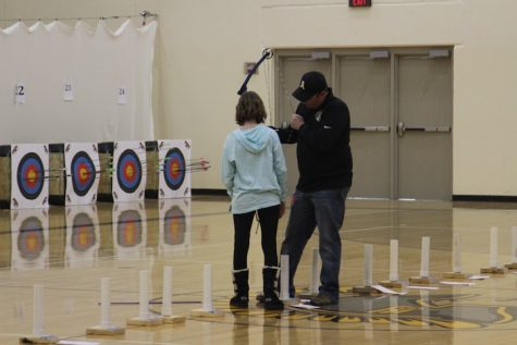 A middle school girl receives help with her bow before taking a shot.