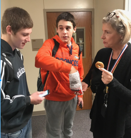 TASTES LIKE SUCCESS - Junior Colton Mudd, freshman Cale Roller, and English teacher Allison Berryhill try the warm mini donuts that will be served at Coffee 7 coffee house.