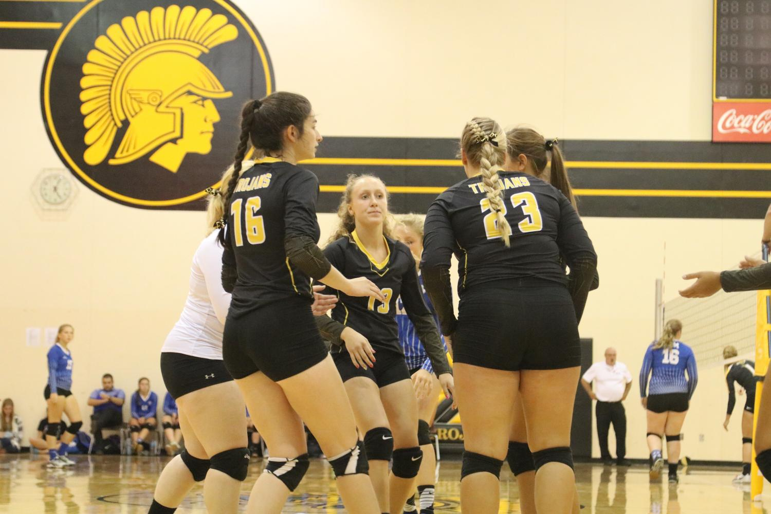Team comes together after  a point in a game against Earlham. Photo Credit: Hannah Alff