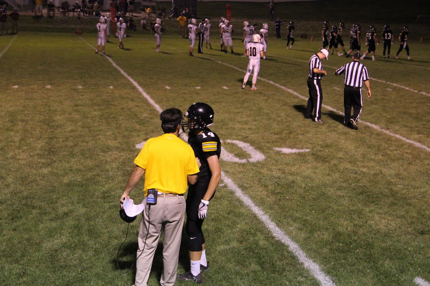 Sophomore Wide Receiver Tyler Moen gets the play from Head Coach Mike McDermott.