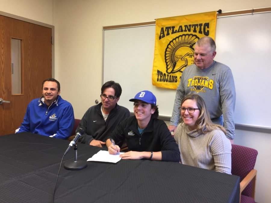 SDSU Coach Brady Banse, Mike McDermott, Cooper McDermott, Christa McDermott, and Gaylord Schelling gather in the conference room to witness Cooper's signing of his letter of intent.