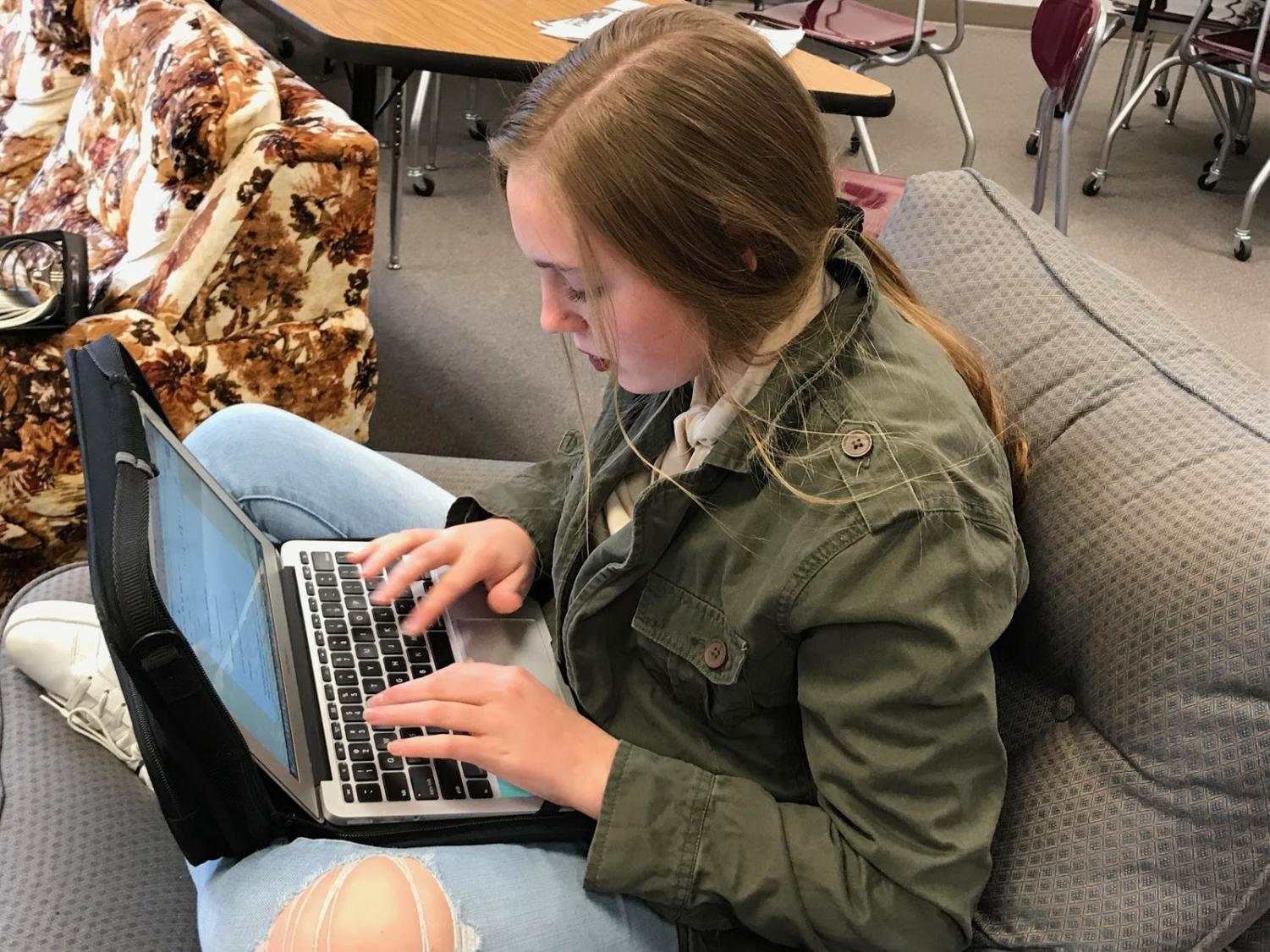 WORKING HARD - Alyssa Brockob writes on her laptop during free time in class. Students who submitted work to Hot Dish used pieces made in and out of school.