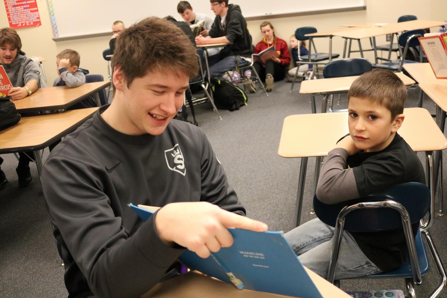 Junior Korben Petersen smiles while reading to Washington student.