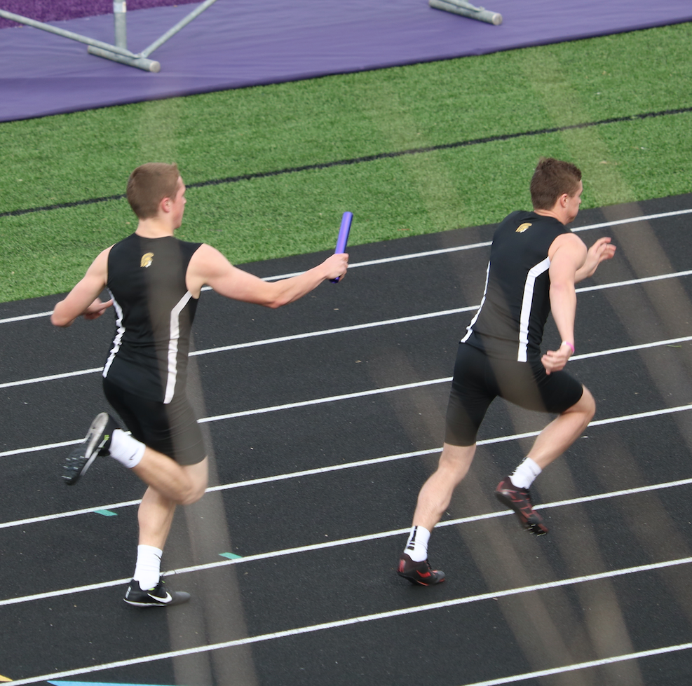 Sophomore Tyler Moen hands the baton to senior Dillon Sonntag during a relay.