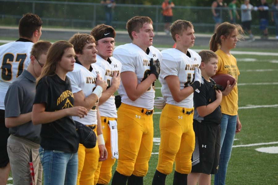 Senior+players+stand+with+their+hands+over+their+hearts+as+the+National+Anthem+plays+before+the+game+against+Saydel.