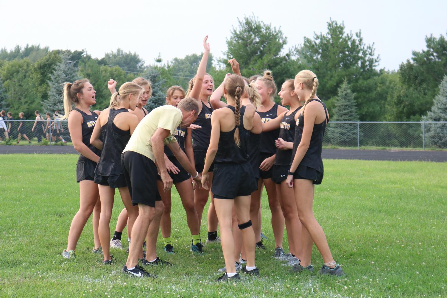 HANDS IN-- Members of the girls cross country team break down with assistant coach Brad Rasmussen before running the time trial course.