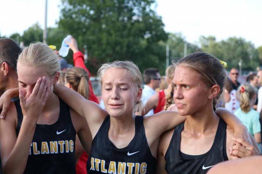 A HELPING HAND - Madison Botos and Taylor McCreedy help fellow teammate Abby Altman after a tough race.