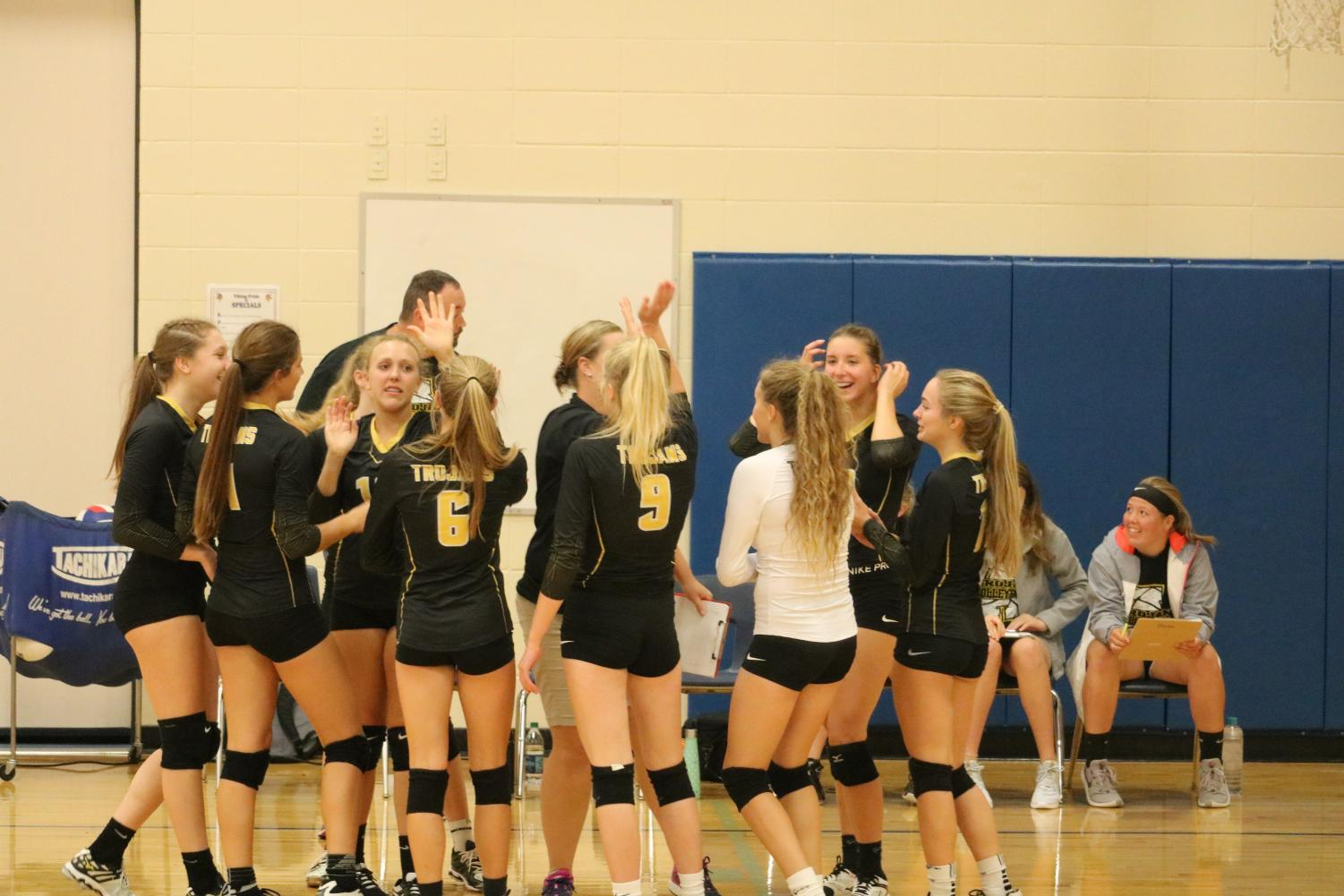 High fives are given all round by the volleyball girls before the start of a new set.