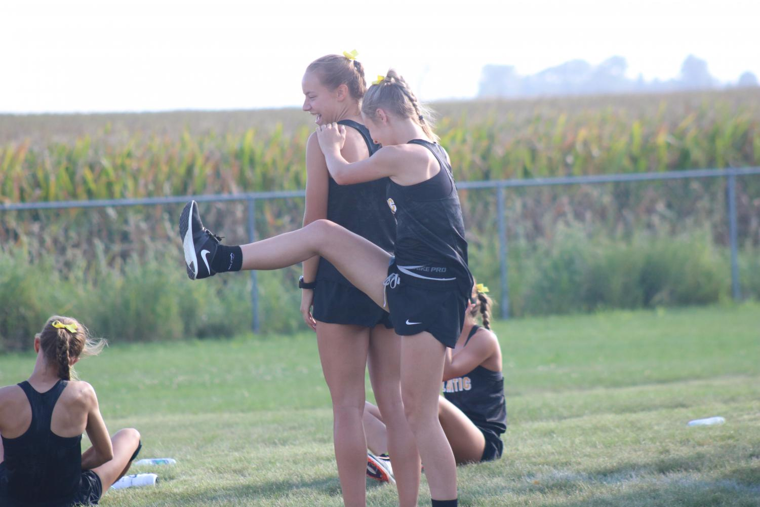 GETTING FOCUSED- Freshman Addie DeArment uses junior Pluma Pross to help her stretch before the race. Other members of the varsity team were stretching before the race at Dallas-Center Grimes.