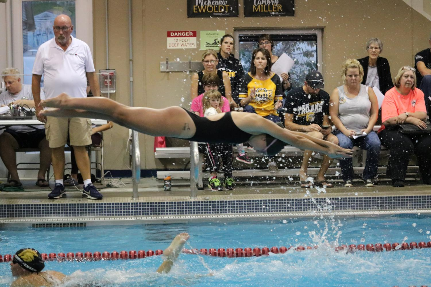 FLYING HIGH -Senior Cambry Miller jumps from the block to continue a relay.  Miller has swum all four years of high school and is one of two seniors on the team.