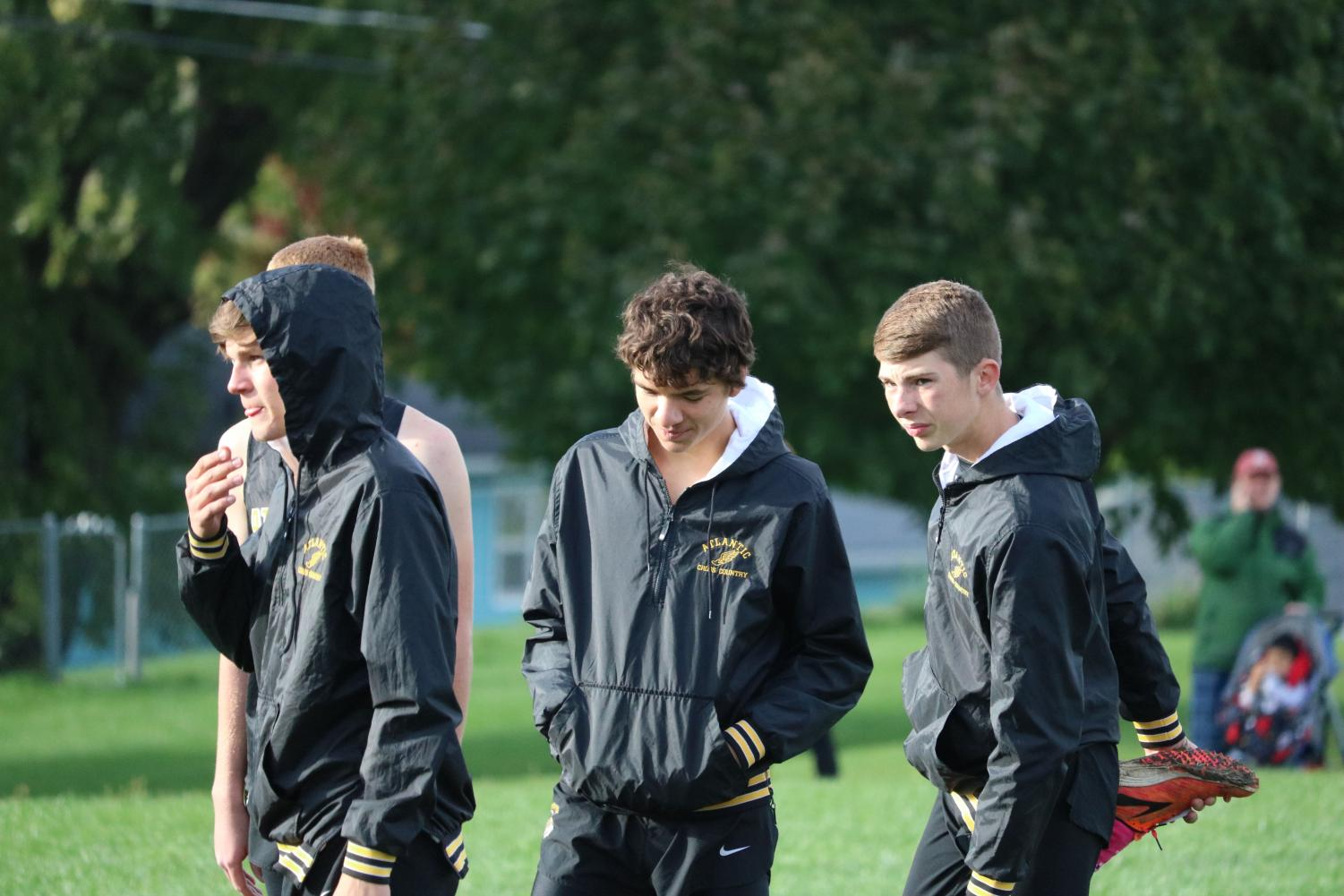 PATIENTLY WAITING-  Bradley Dennis, Jalen Petersen, and Cooper Jipsen stretch at the Trojan Invitational before the start of their race. Varsity boys placed eighth at the meet.