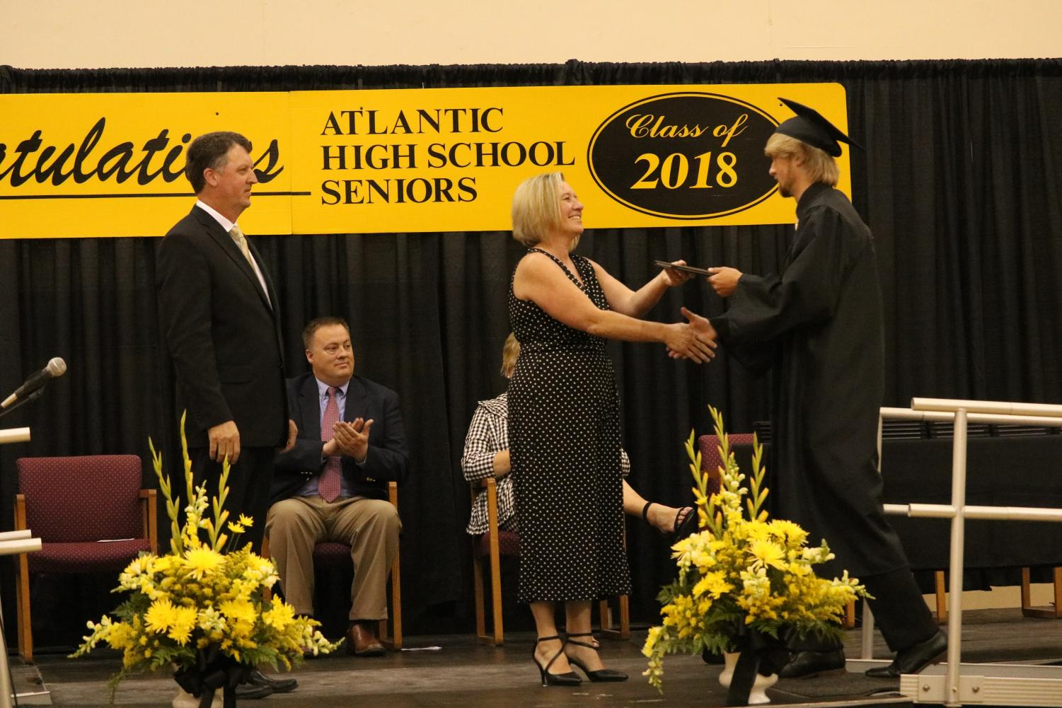CONGRATULATIONS - 2018 graduate Brady Dickerson shakes hands with Board of Education member Allison Bruckner. Graduates received their diplomas at commencement last May.