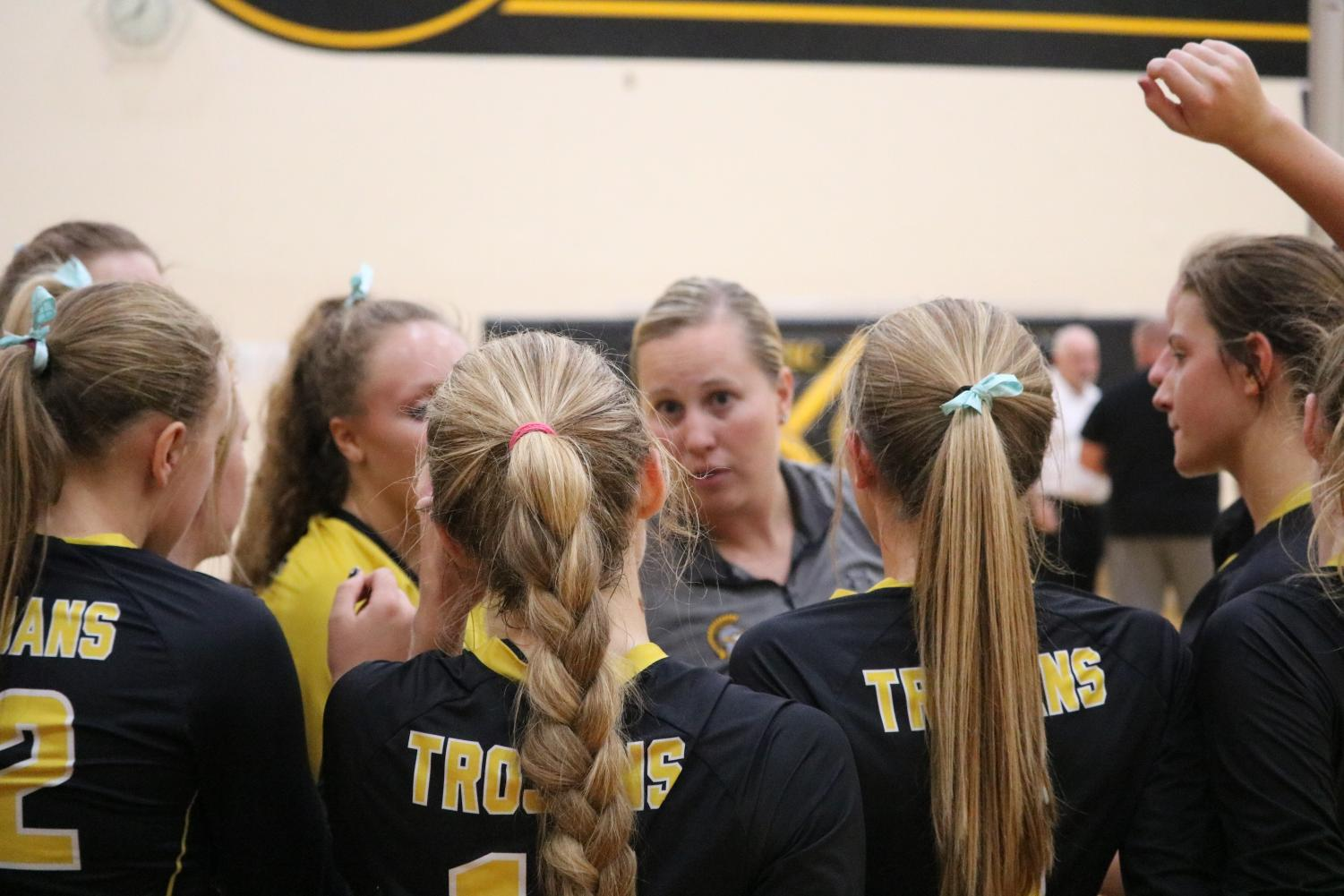 The volleyball girls listen intently to Coach Blake's instructions before heading out onto the court.