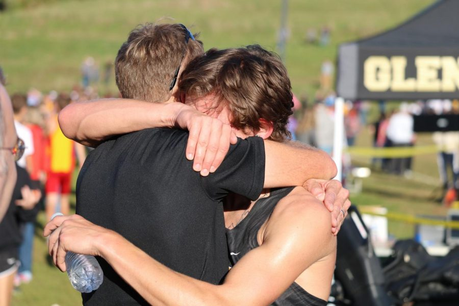TEARS OF JOY -- Assistant coach Brad Rasmussen embraces junior Bradley Dennis after the conclusion of his race. Dennis placed 14th, earning an individual qualification and helping his team qualify as well.