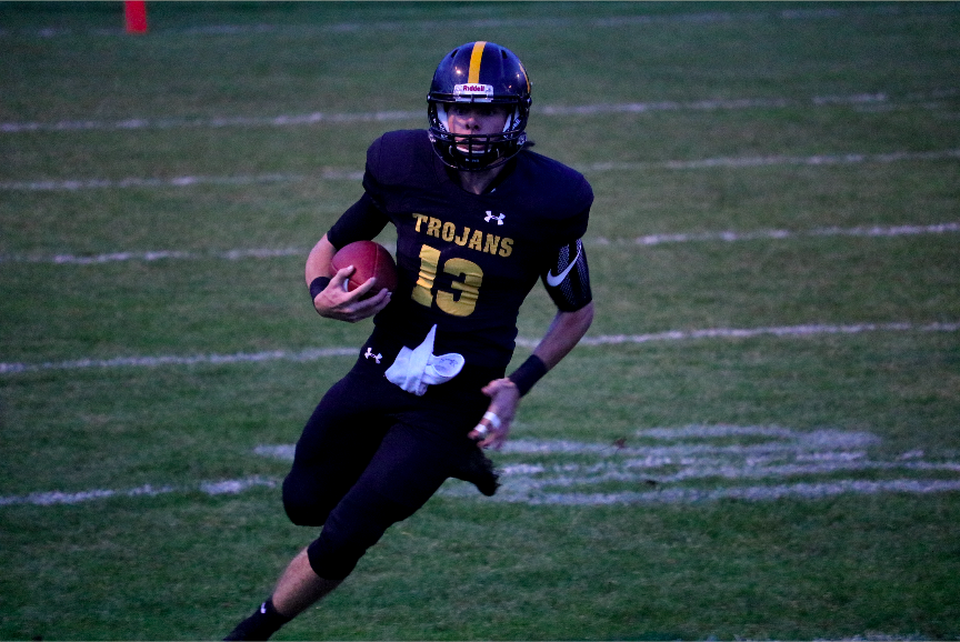 Quarterback, Chase Mullenix looks to run for a first down, as he surveys the field.