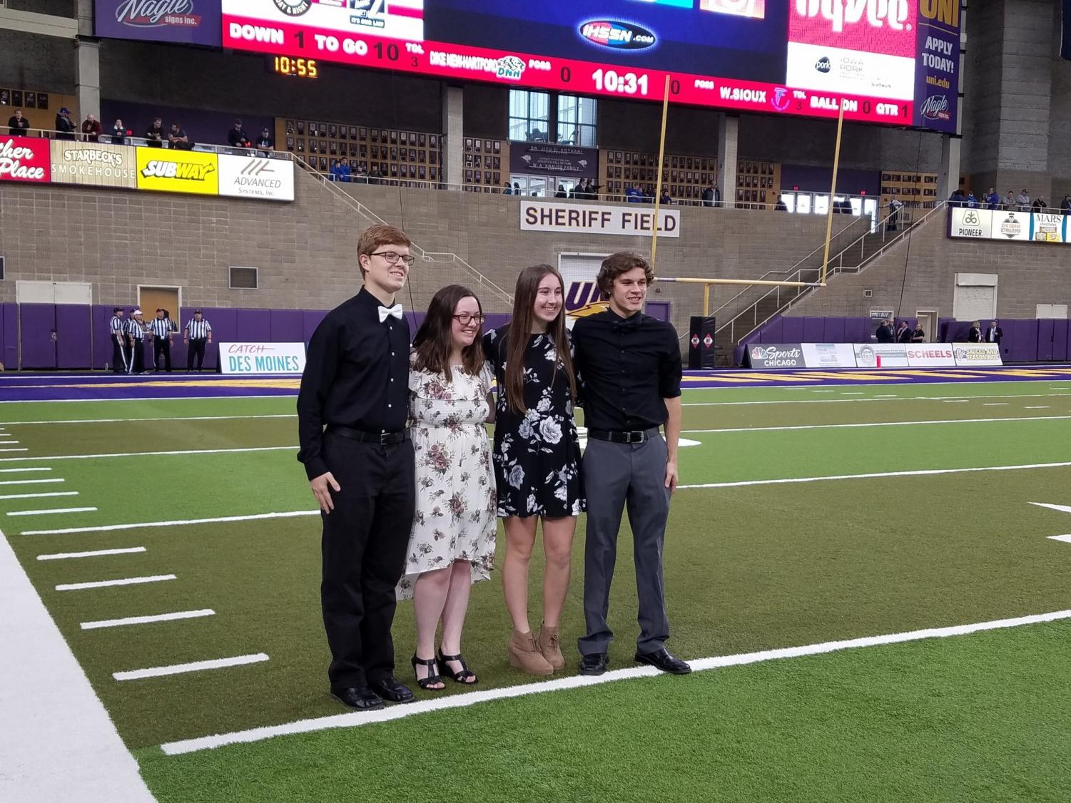 OH SAY CAN YOU SEE - Performing AHS choir members pose for a picture on the field of the UNI Dome. The quartet consisted of Chris Krogh, Ana Muell, Katie Saluk and Bradley Dennis.