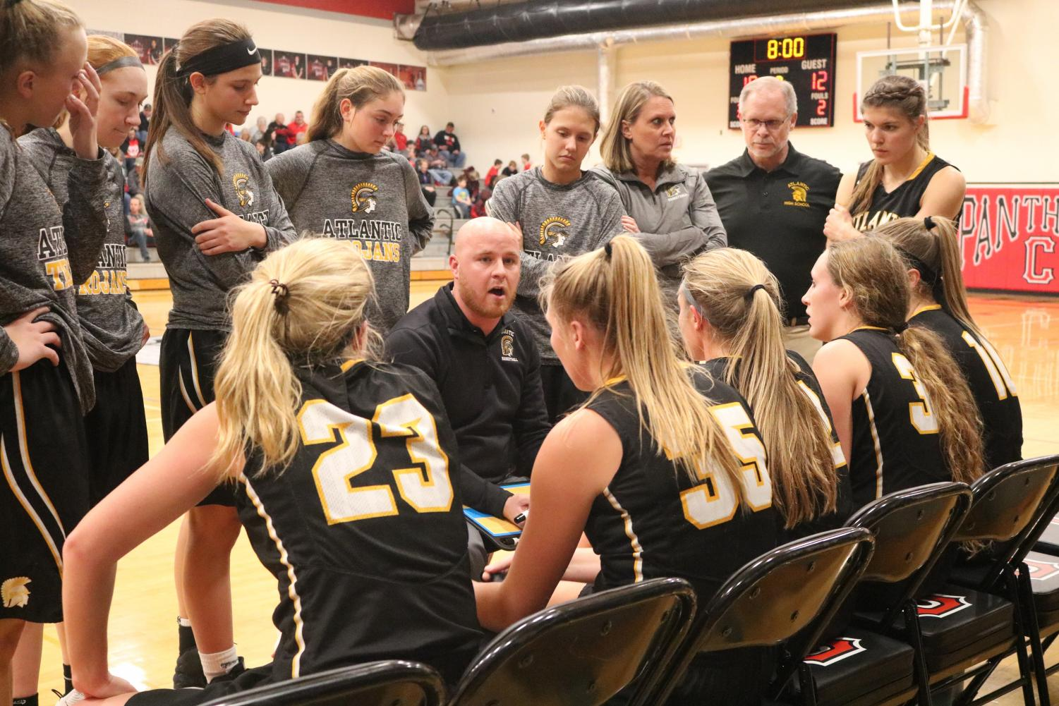 The varsity girls listen intently to Coach Vargason during a timeout. Sophomore Alyssa Derby led the Trojan pack with 13 points.
