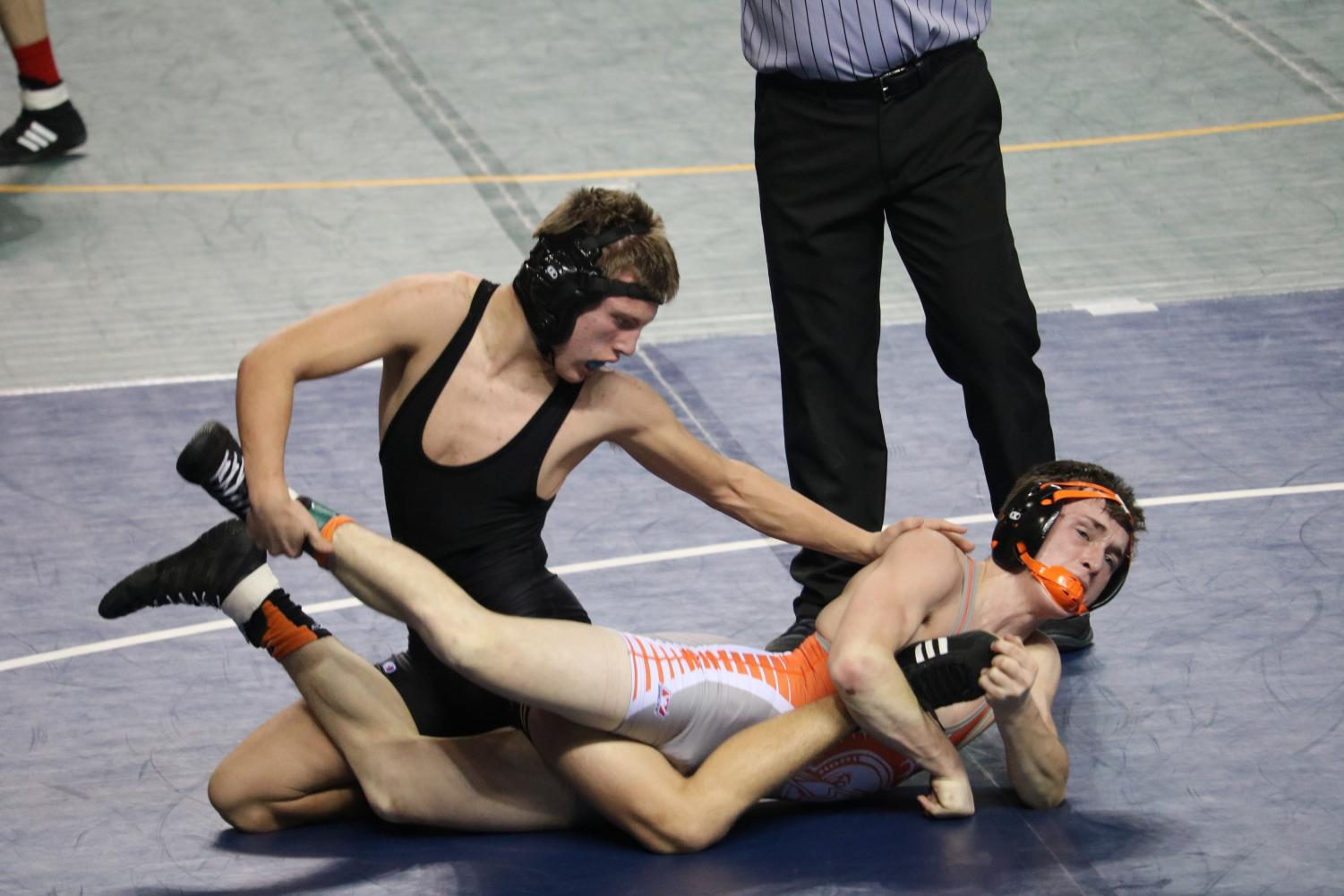 STAY DOWN- Sophomore Steele McLaren pushes his opponent down during his match at the Council Bluffs Classic. S. McLaren ended the night at OA-BCIG with one pin and received a forfeit.