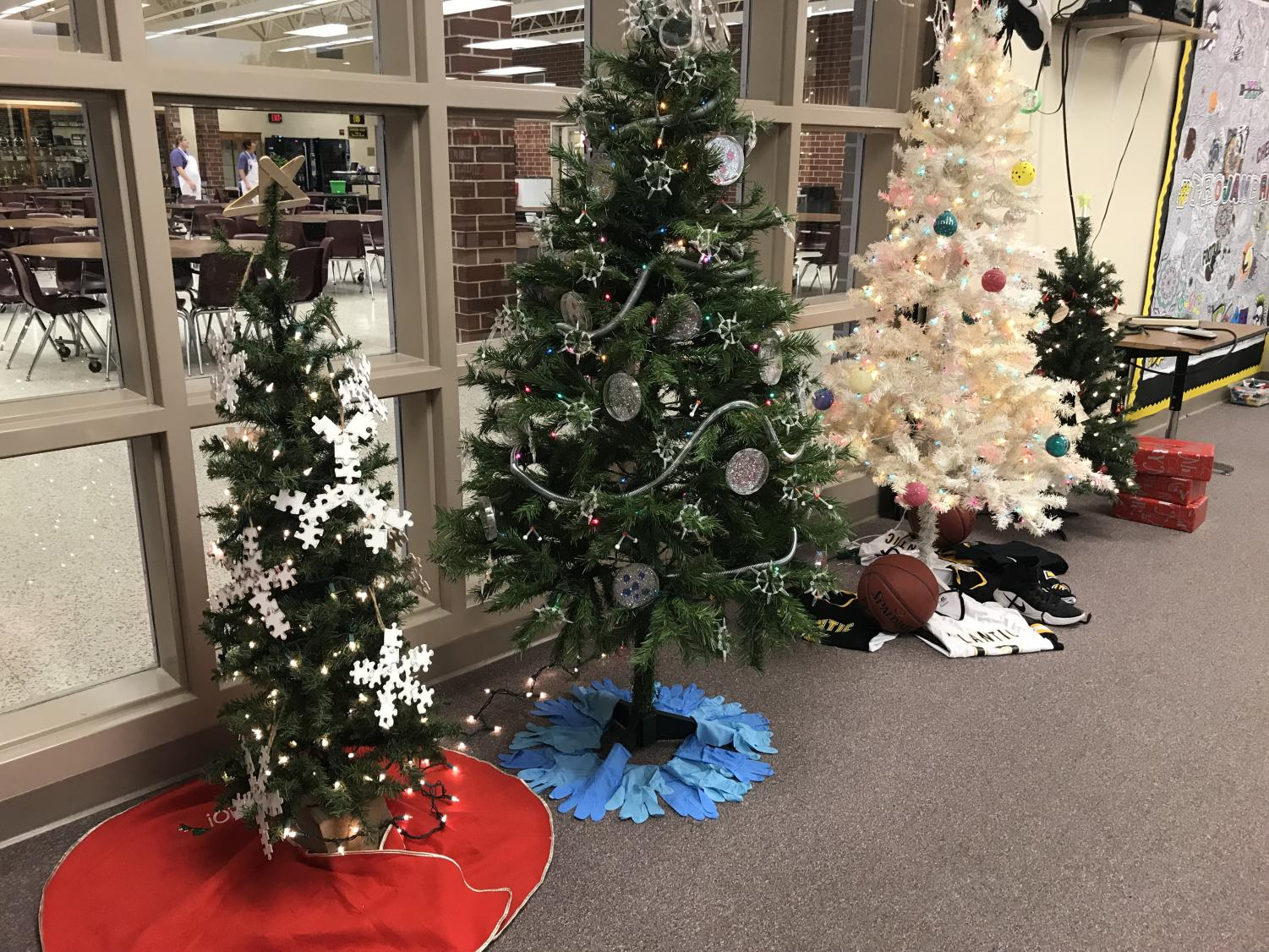 SPREADING CHEER - Christmas trees are being displayed in the media center for the remainder of the semester. Students can vote for their favorite trees during the week of semester tests by dropping money into boxes set in front of each activity's tree.