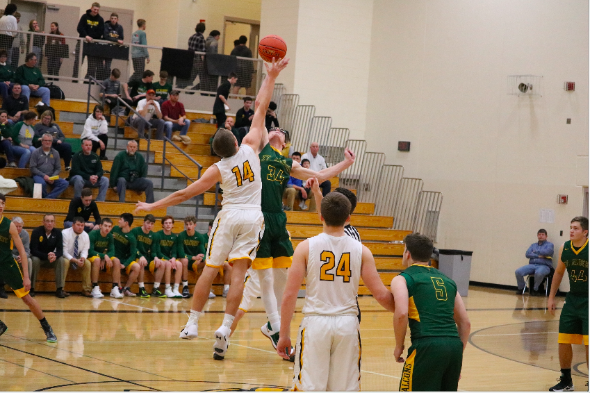 JUMPMAN - Junior Tyler Moen leaps to grab the ball at the beginning of the game. Moen has been an asset the basketball team for three years.