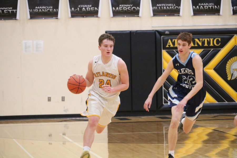 EYES ON THE PRIZE- Senior Logan Reilly focuses as he dribbles down the court. Reilly finished the game with 10 total points.