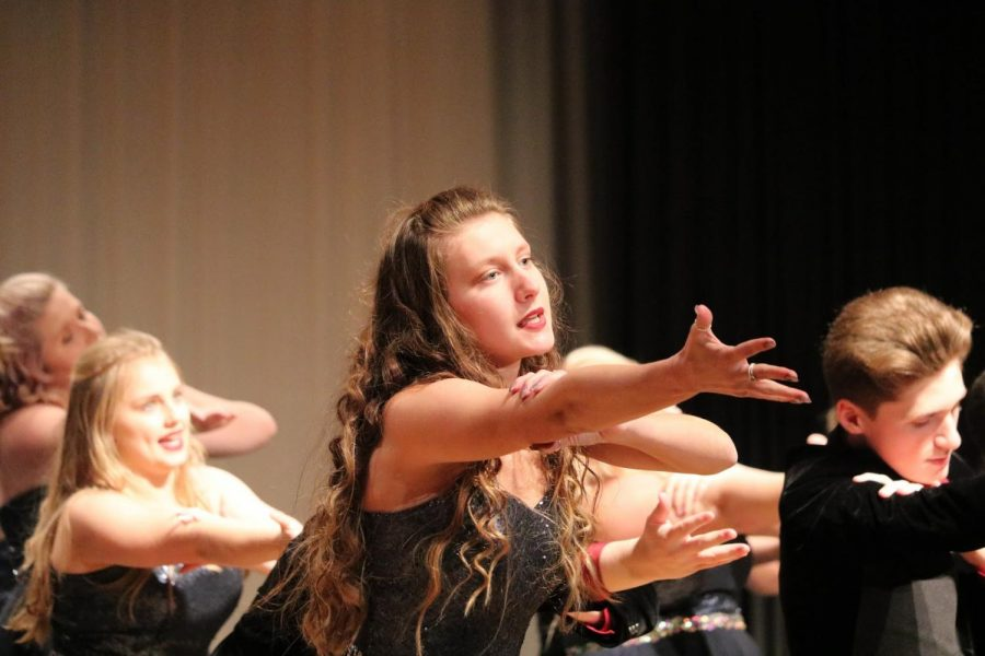 """REACHING OUT - Senior Cambry Miller reaches toward the audience during the Premiere performance. Premieres show has six songs, including """"Rise/New Revolution,"""" """"Hero,"""" """"Never Alone,"""" """"Holding Out for a Hero,"""" """"Larger than Life"""" and """"Immortals."""" They will work to perfect and perform this show all season."""