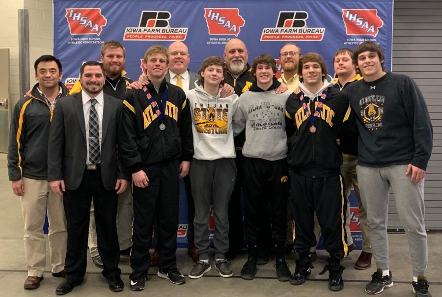 AFTER THE FACT - Trojan participants stand with their wrestling staff after the awards ceremony. Seniors Chase McLaren and Connor Pellett left the tournament with second place and eighth place medals, respectively. The remaining three - junior Cale Roller, sophomore Joe Weaver and freshman Garrett McLaren - all hope to return and earn medals of their own in the future.