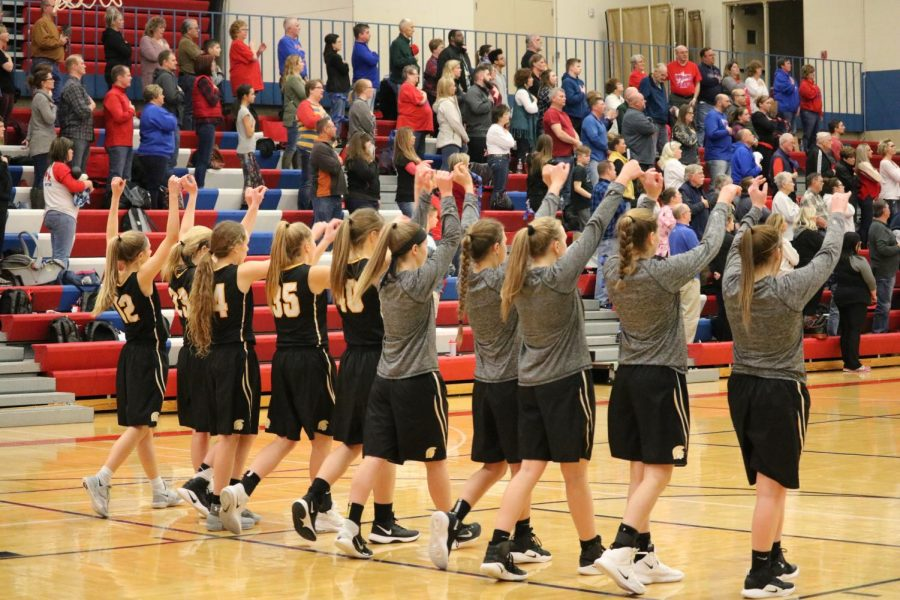 The+varsity+girls+throw+their+hands+in+the+air+after+the+conclusion+of+the+National+Anthem.+The+win+against+Council+Bluffs+Abraham+Lincoln+is+third+of+the+season+for+the+Trojan+girls%2C+as+they+have+also+topped+Saint+Albert+and+Clarinda+this+year.