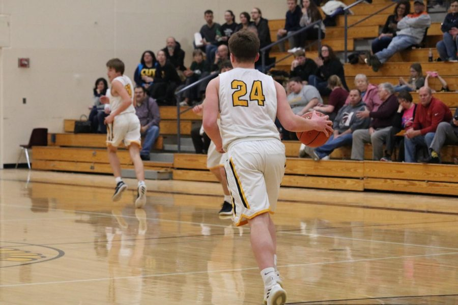 Senior+Logan+Reilly+dribbles+the+ball+up+the+floor+in+the+Trojan+gym.+Currently%2C+he+leads+his+team+in+rebounds+with+130.