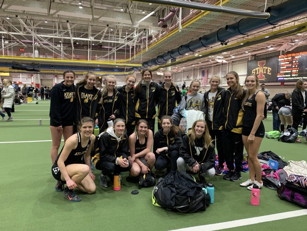 GETTING STARTED - the Trojan girls' track team smiles on the infield of the indoor track at Iowa State. The first two meets of the season proved successful for many members of the team.