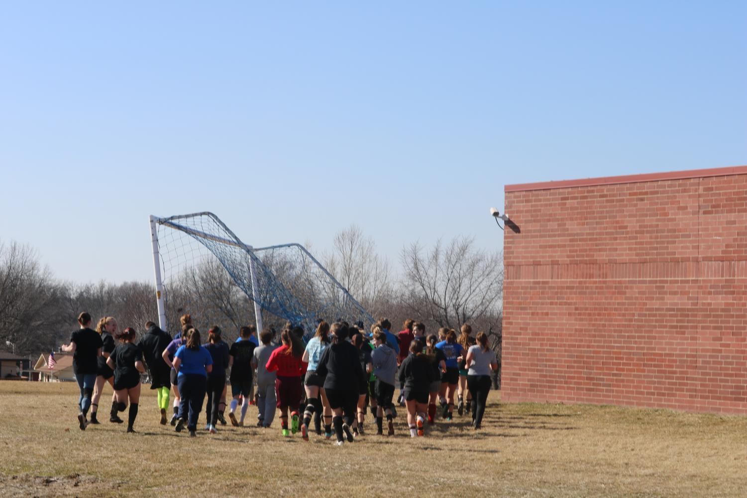 SOCCER KNOWS NO GENDER -- The boys' and girls' teams work together to bring a net from the game field to the practice field.