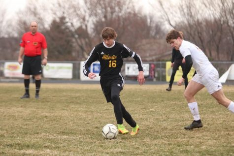 ON THE ATTACK - Senior Nathan Brockman dribbles the ball away from the Tri-Center competitor. Brockman is one of the captains for the boys