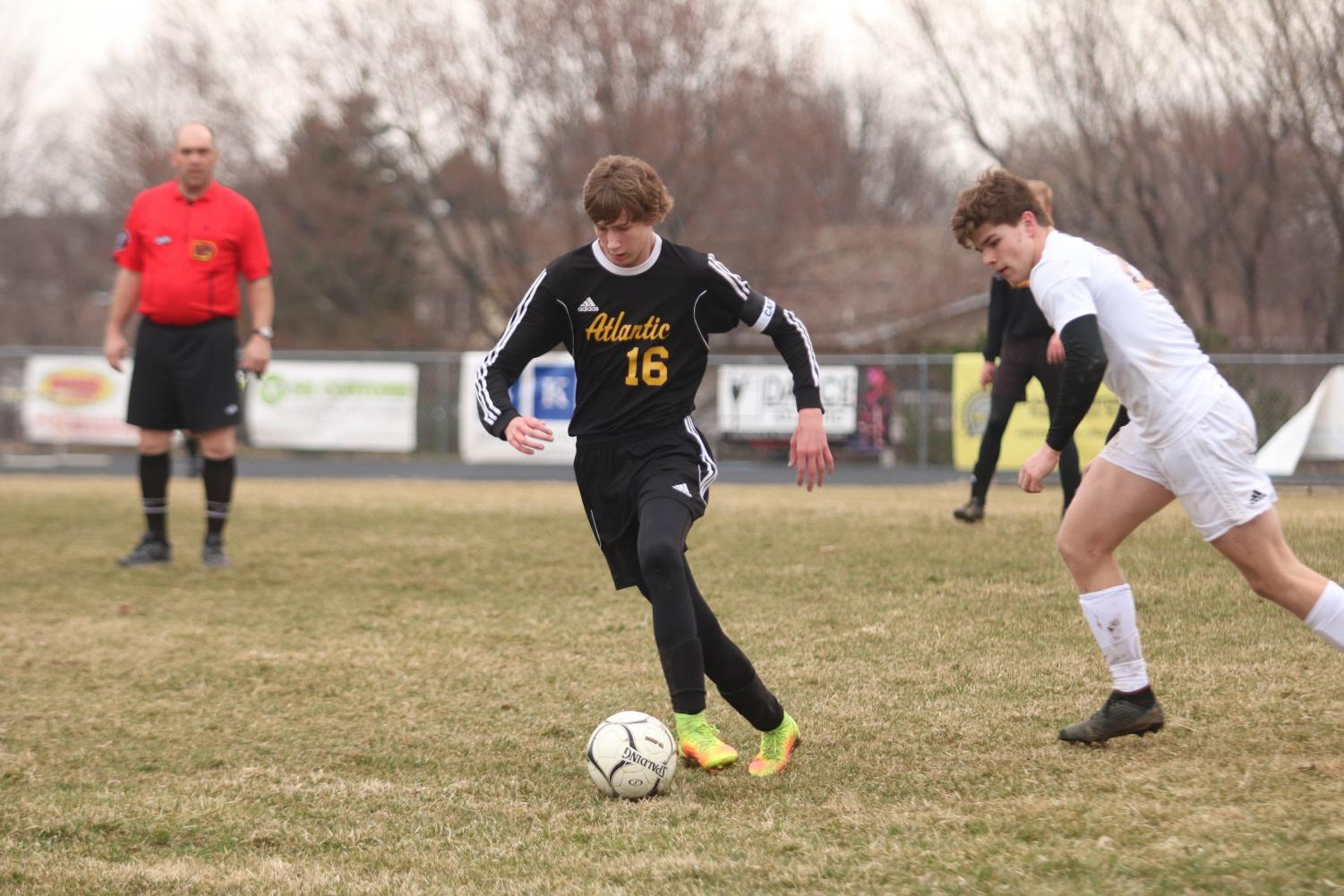 ON THE ATTACK - Senior Nathan Brockman dribbles the ball away from the Tri-Center competitor. Brockman is one of the captains for the boys' soccer team this year.