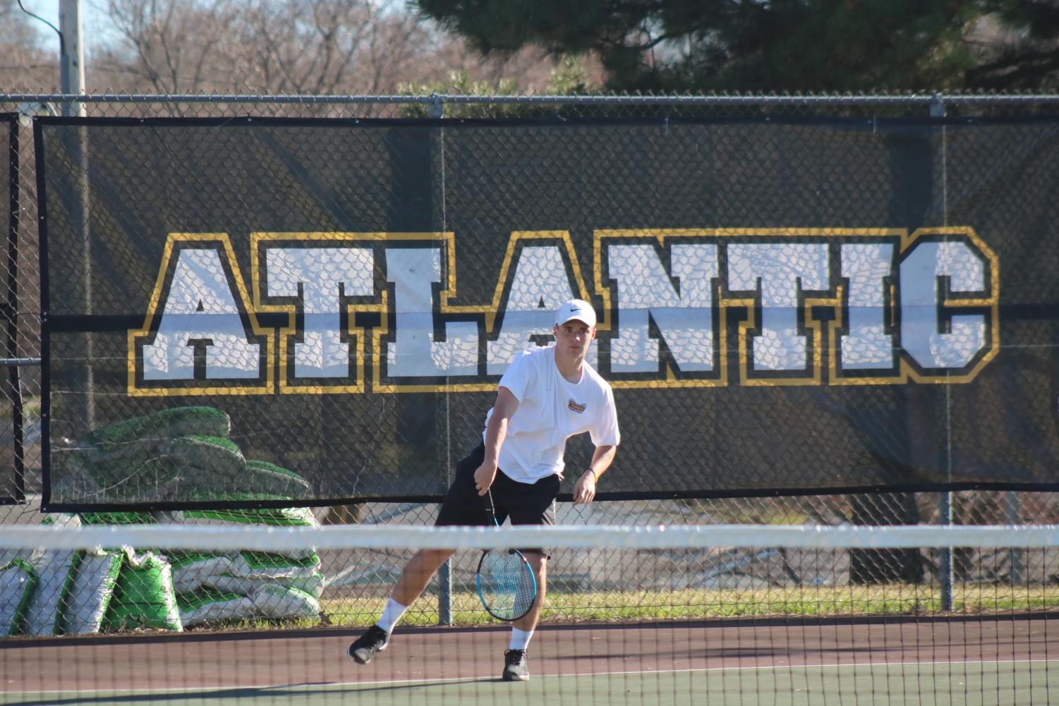 Junior Nile Petersen swings through his serve at the Washington tennis courts. Petersen is undefeated at the #1 spot.