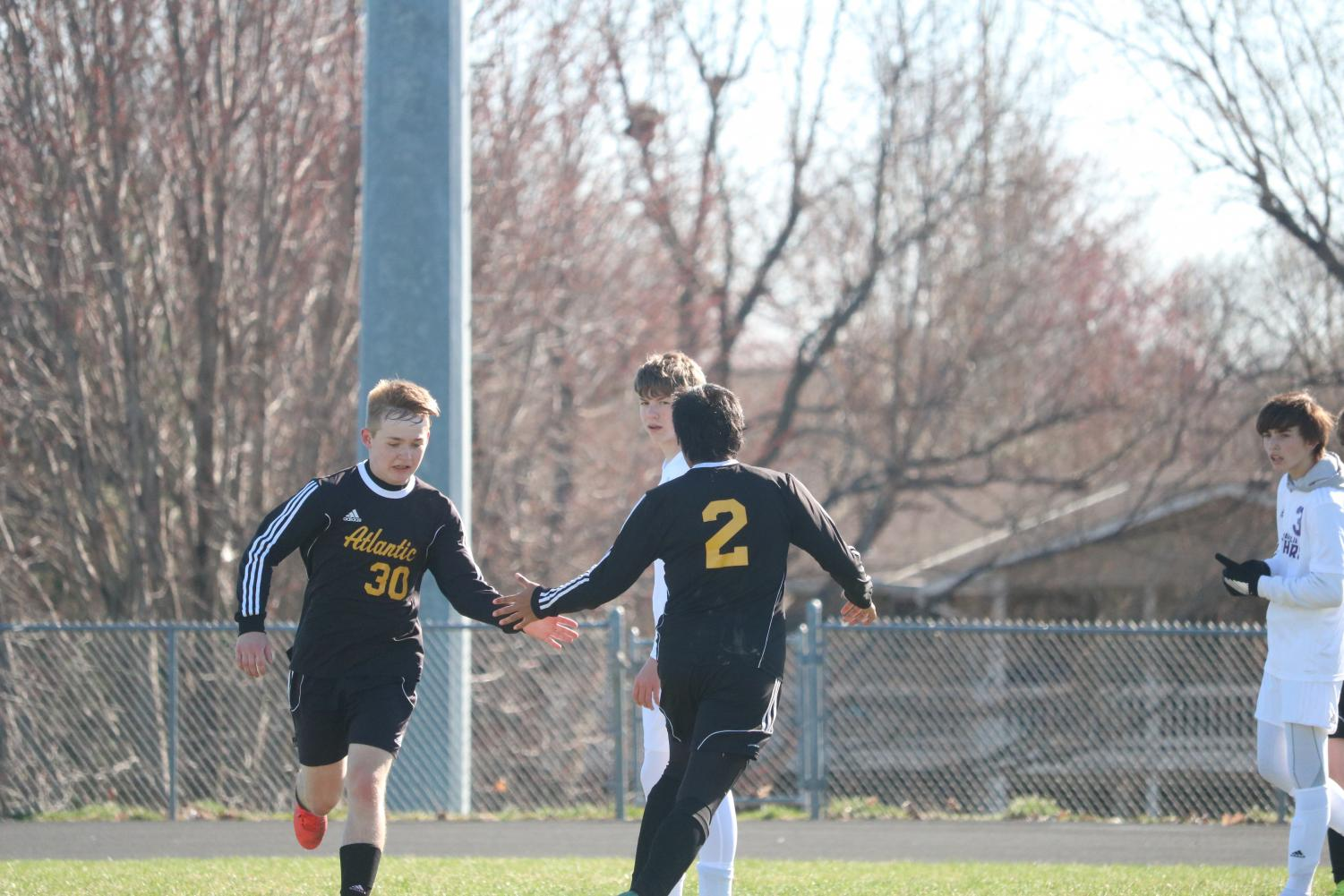 TAKING A BREAK - Senior Brainhart Buliche subs in for junior Zach Mathisen and gives him the typical high-five seen during this process. This is Mathisen's first year of playing soccer in high school.
