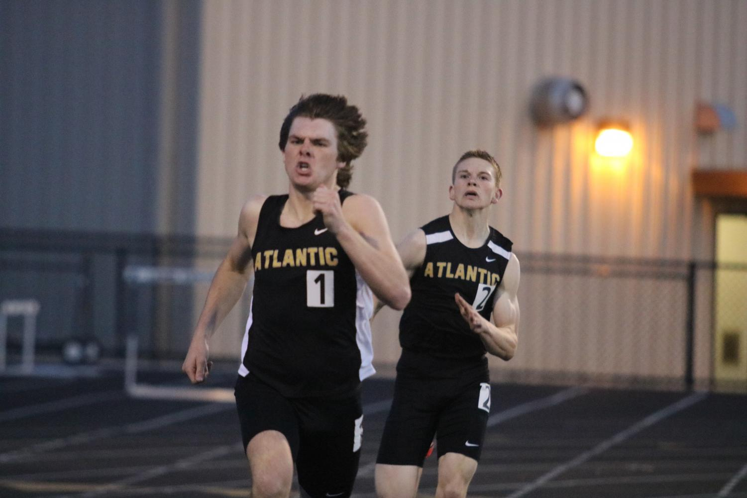 WORKING TOGETHER - Senior Chase Mullinex and Sophomore Craig Alan Becker push each other during their race. Mullinex and Becker have been solid runners for the boys' team.