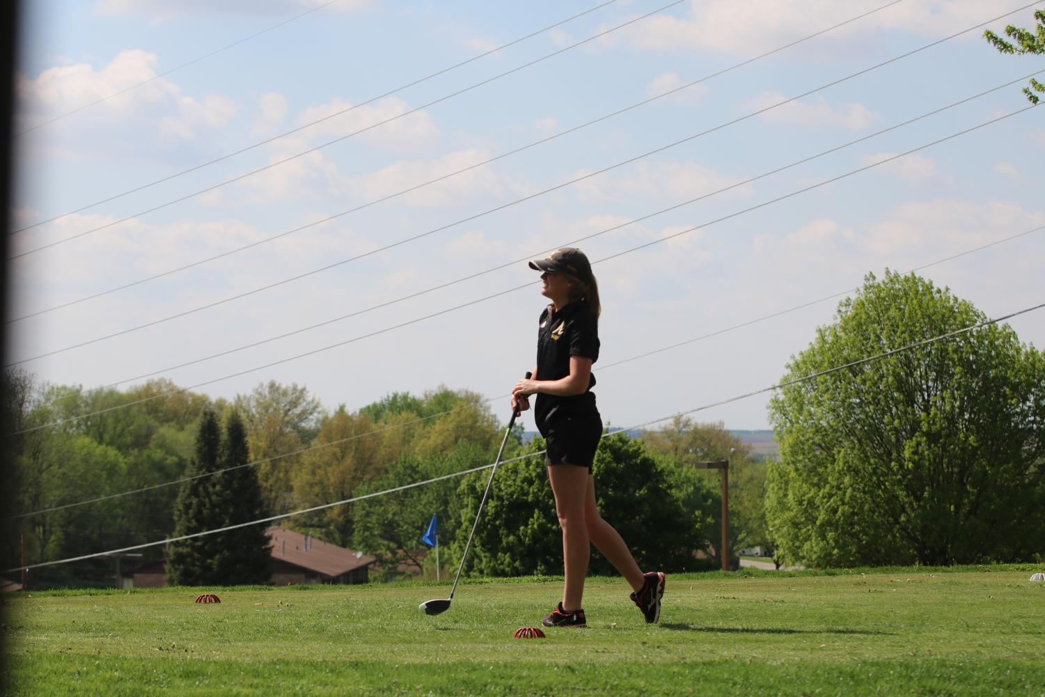 Senior Baylee Newell watches her drive from the tee off spot. Newell was a medalist at Denison-Schleswig with a score of 43.