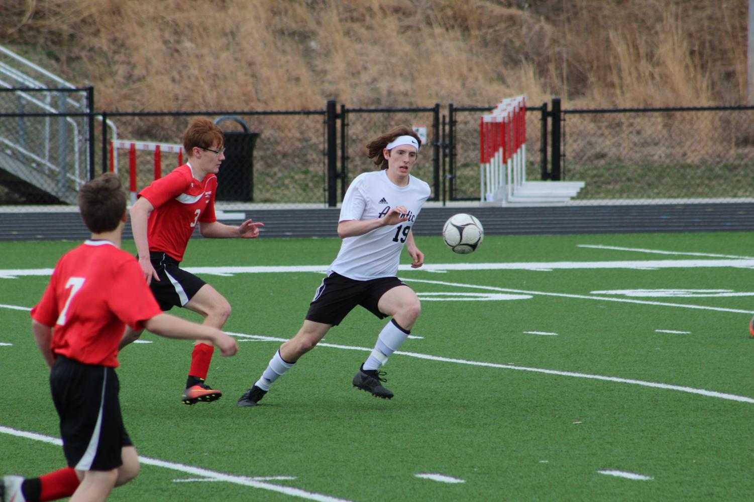 NOT ON MY WATCH - Junior Jackson Mullin races to beat his opponent to the ball. Mullin plays defense for the Trojans and has participated in soccer since his freshman year.