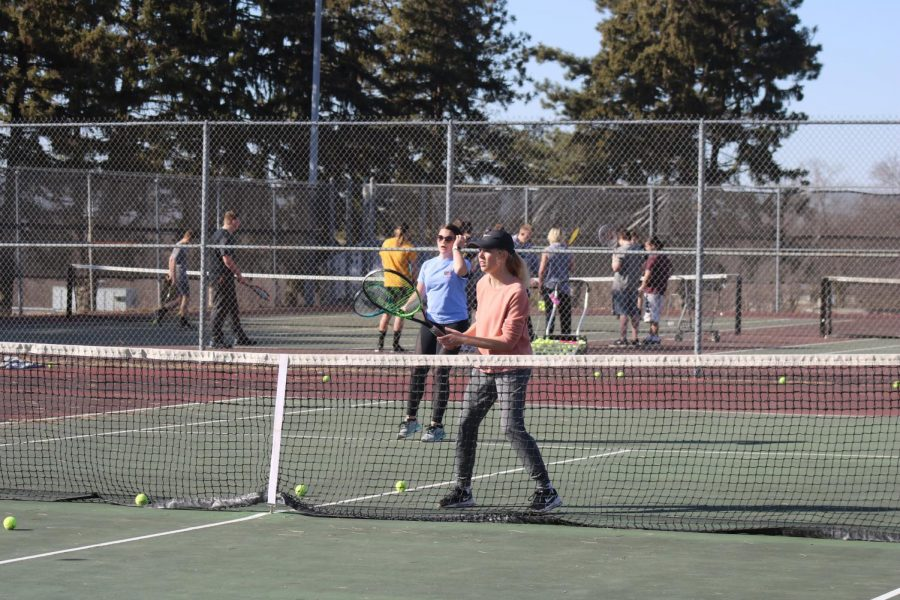 PRACTICE+MAKES+PERFECT-+Junior+Hana+Holtz+and+sophomore+Makynzie+Steffens+practice+doubles+at+the+Washington+tennis+courts+in+March.