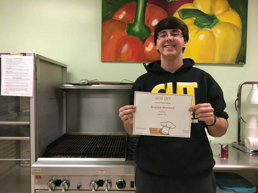 COOKIN%27+UP+THE+COMPETITION+-+Senior+Brandon+Woodard+poses+with+a+certificate+to+signify+his+win+in+the+grilled+cheese+contest.+Woodard+has+taken+many+culinary+arts+courses+throughout+high+school+and+has+won+two+official+contests.