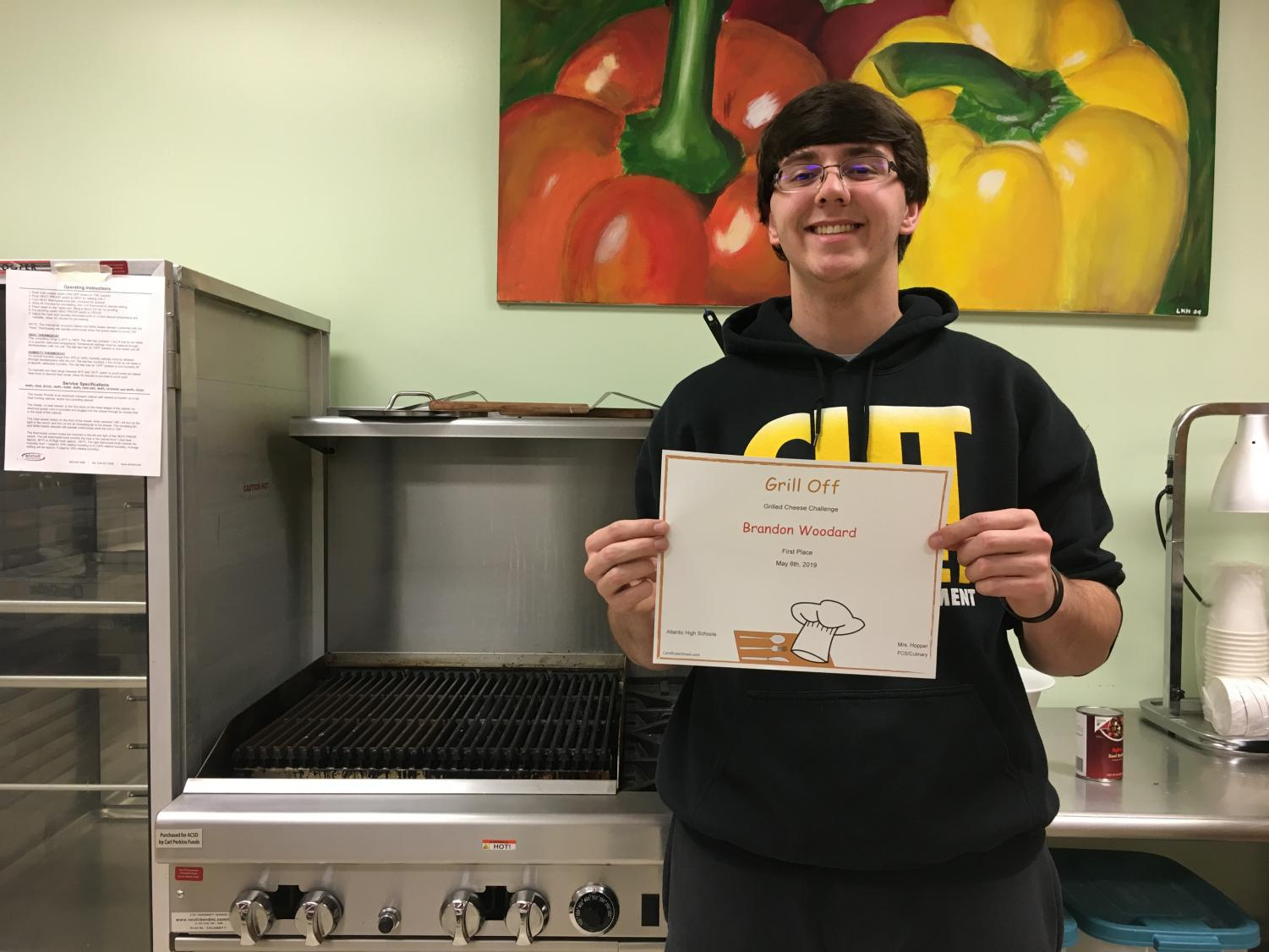 COOKIN' UP THE COMPETITION - Senior Brandon Woodard poses with a certificate to signify his win in the grilled cheese contest. Woodard has taken many culinary arts courses throughout high school and has won two official contests.