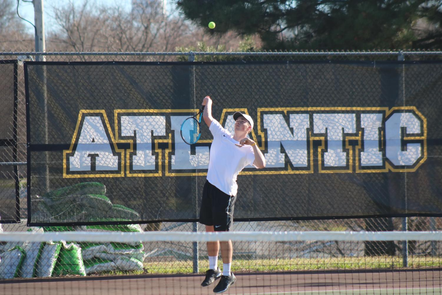 Junior Nile Petersen serves the ball to his opponent. Petersen qualified for state for the second year in a row following a successful day at districts.