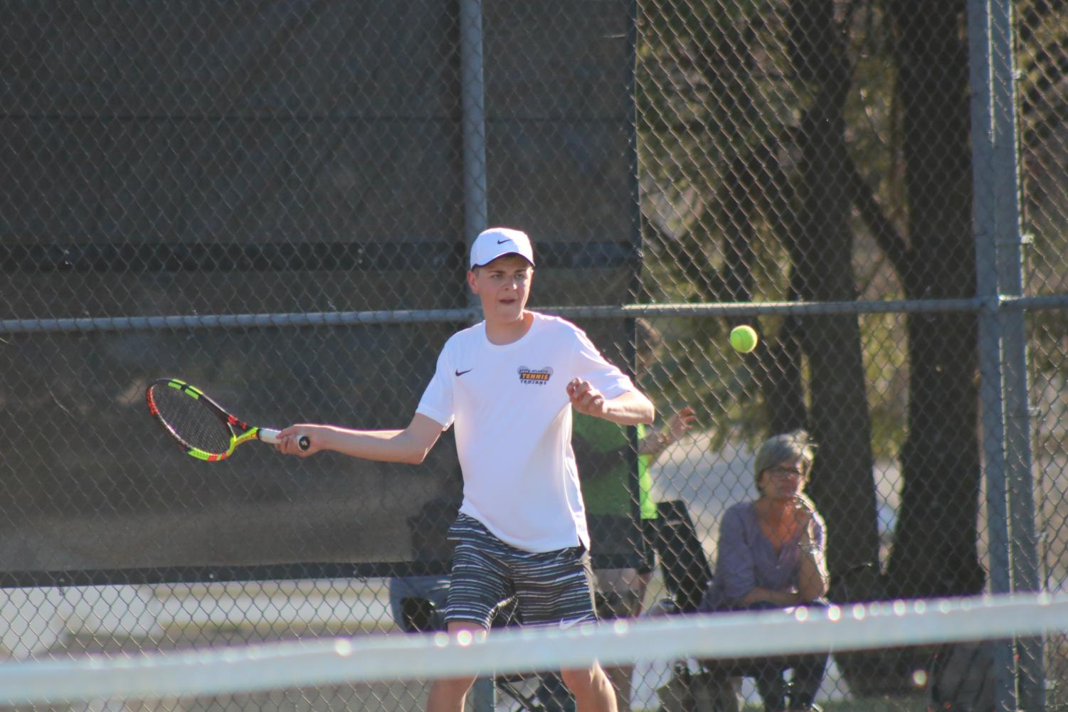 Junior Jesse Reid prepares to hit a forehand to his competitor in the #2 singles match. Reid has played tennis all three years of high school.