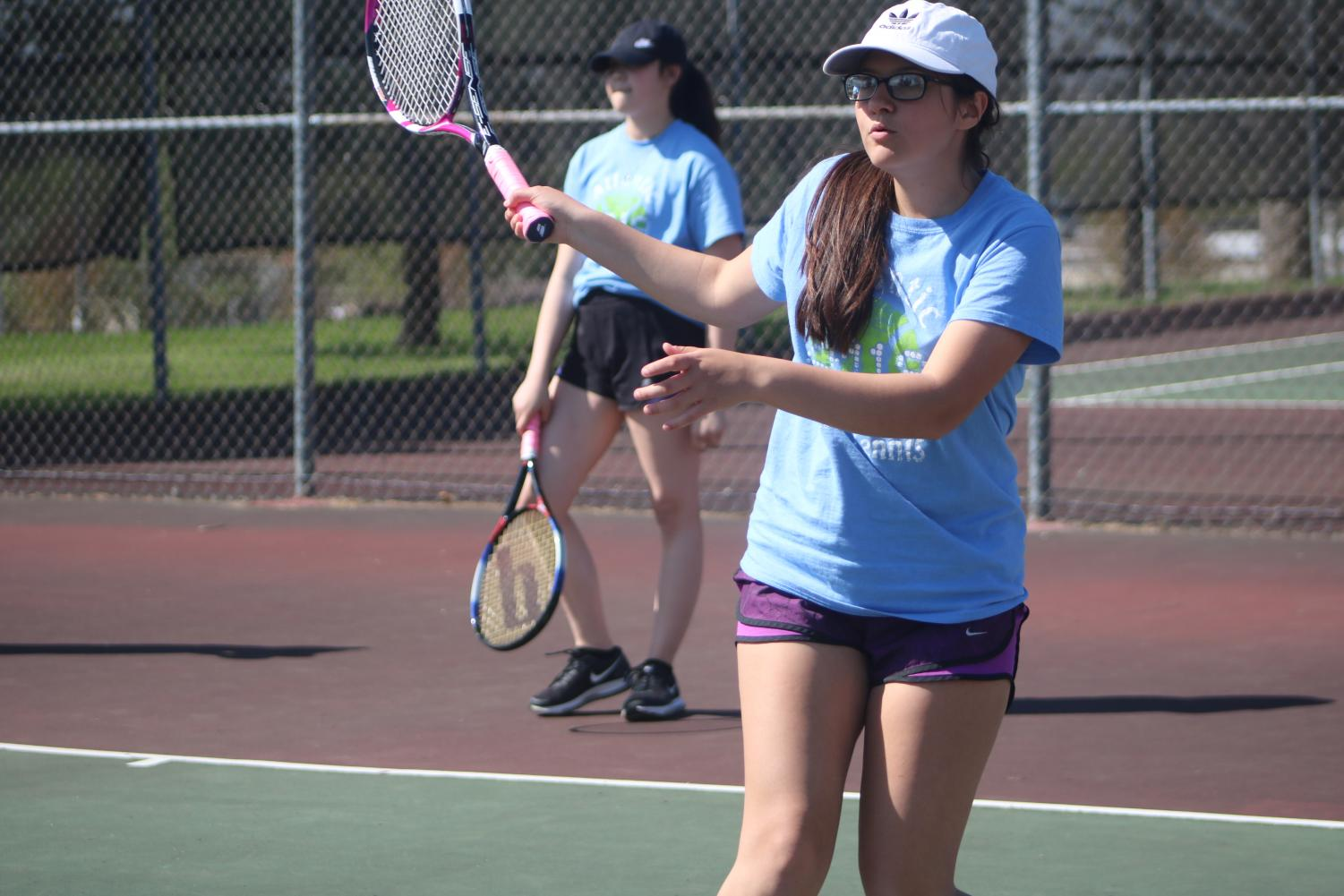 Sophomore Genevieve Martinez eyes her shot in warmups. Martinez won nine matches this season, including a double dip in the history-making win at Harlan.