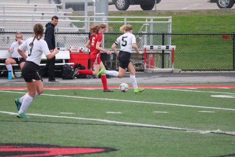 Seniors Erin Wendt and Sadie Welter defend the goal while junior Emma Templeton is patiently waiting to be subbed in.