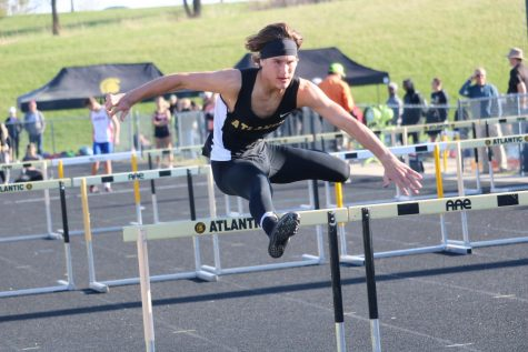 SOARING OVER - Sophomore Joe Weaver leaps over the hurdle during his respective leg of the shuttle hurdle relay. Weaver has participated in track for two years.